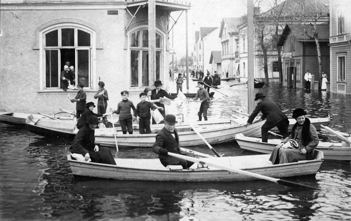 Några roddbåtar i en översvämmad stadskärna i Bollnäs.
