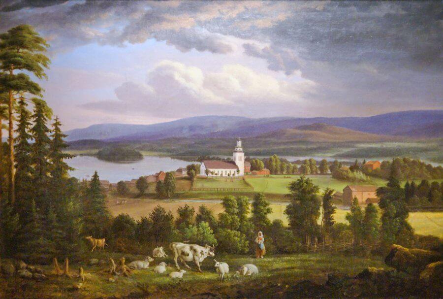 En stor oljemålning av en kyrka i ett vackert landskap i Hälsingland. I förgrunden en vallpiga med kor och får, i bakgrunden blå berg och sjöar.