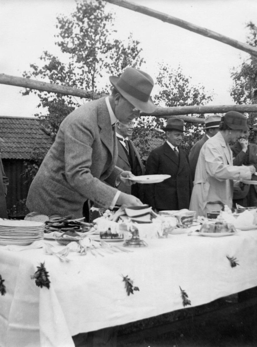 En man förser sig med godsaker från ett smörgåsbord. I bakgrunden syns fler människor som gör samma sak.