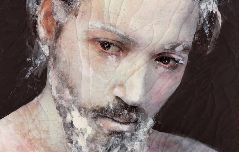 Konstverk föreställande ett mansansikte med vit lödder i skägg och hår.