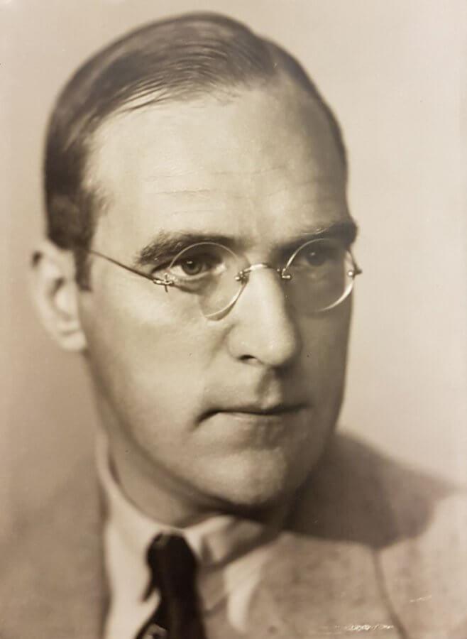 En man på ett studiofotografi, han har runda, stålbågade glasögon.
