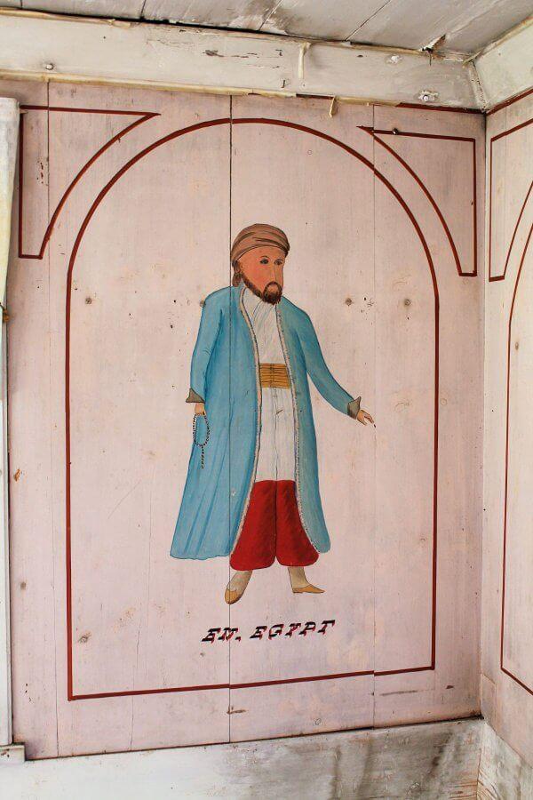 """En väggmålning från en sal i en hälsingegård, den föreställer en man med turban på huvudet, lång rock och pösiga byxor. """"En egypt"""" står det under målningen."""