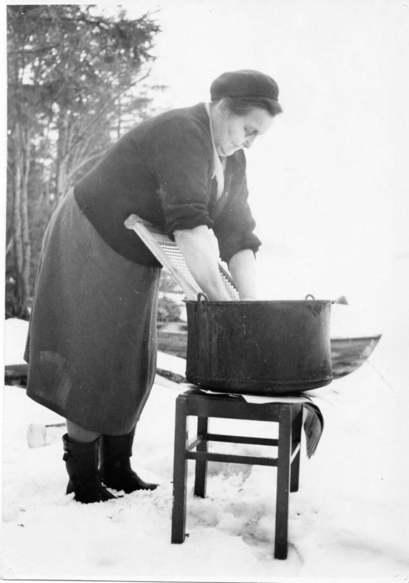 En kvinna tvättar kläder i en balja.