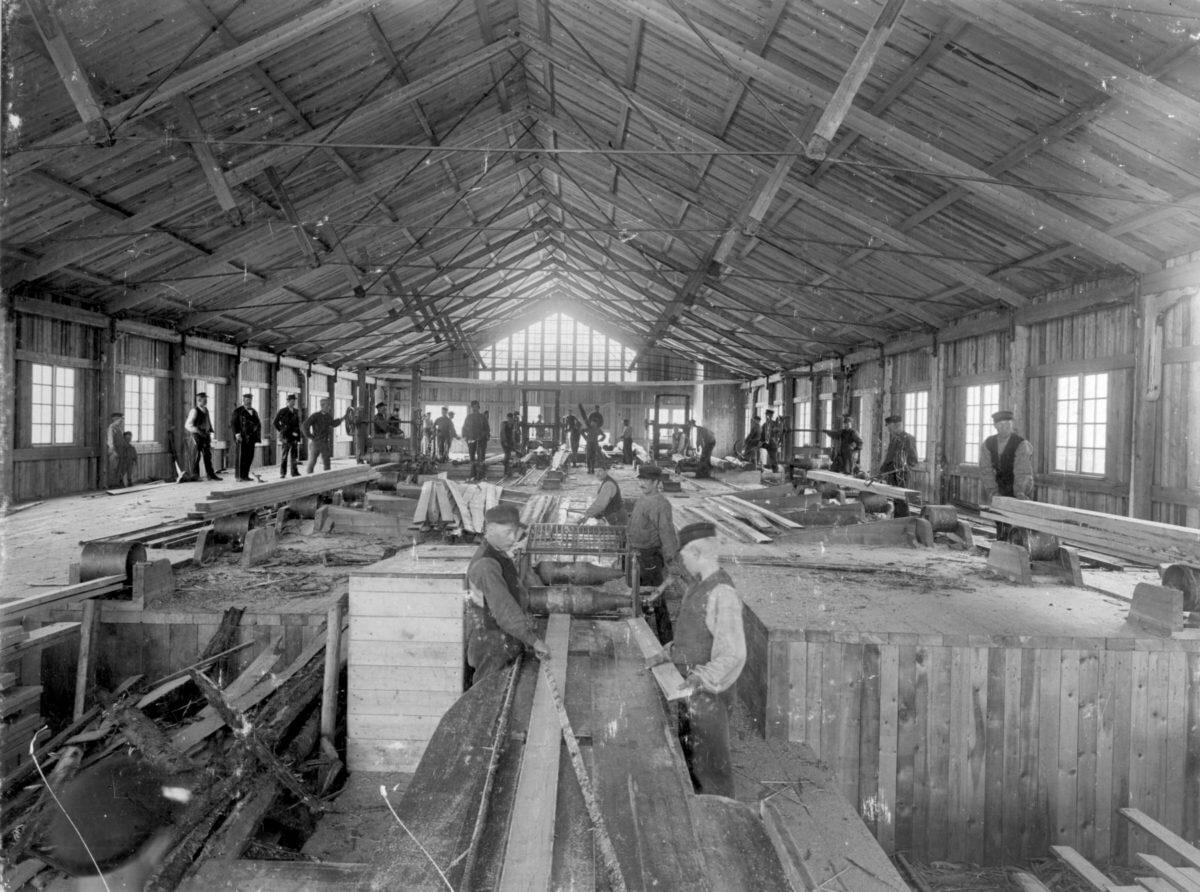 Insidan av ett sågverk med arbetande män och överseende inspektörer.