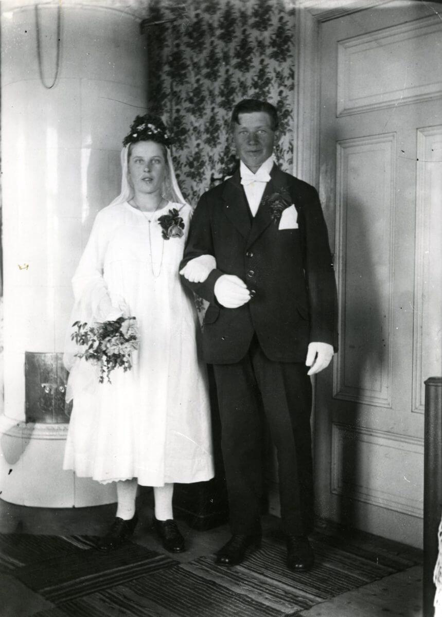 Ett bröllopspar poserar intill en kakelugn.