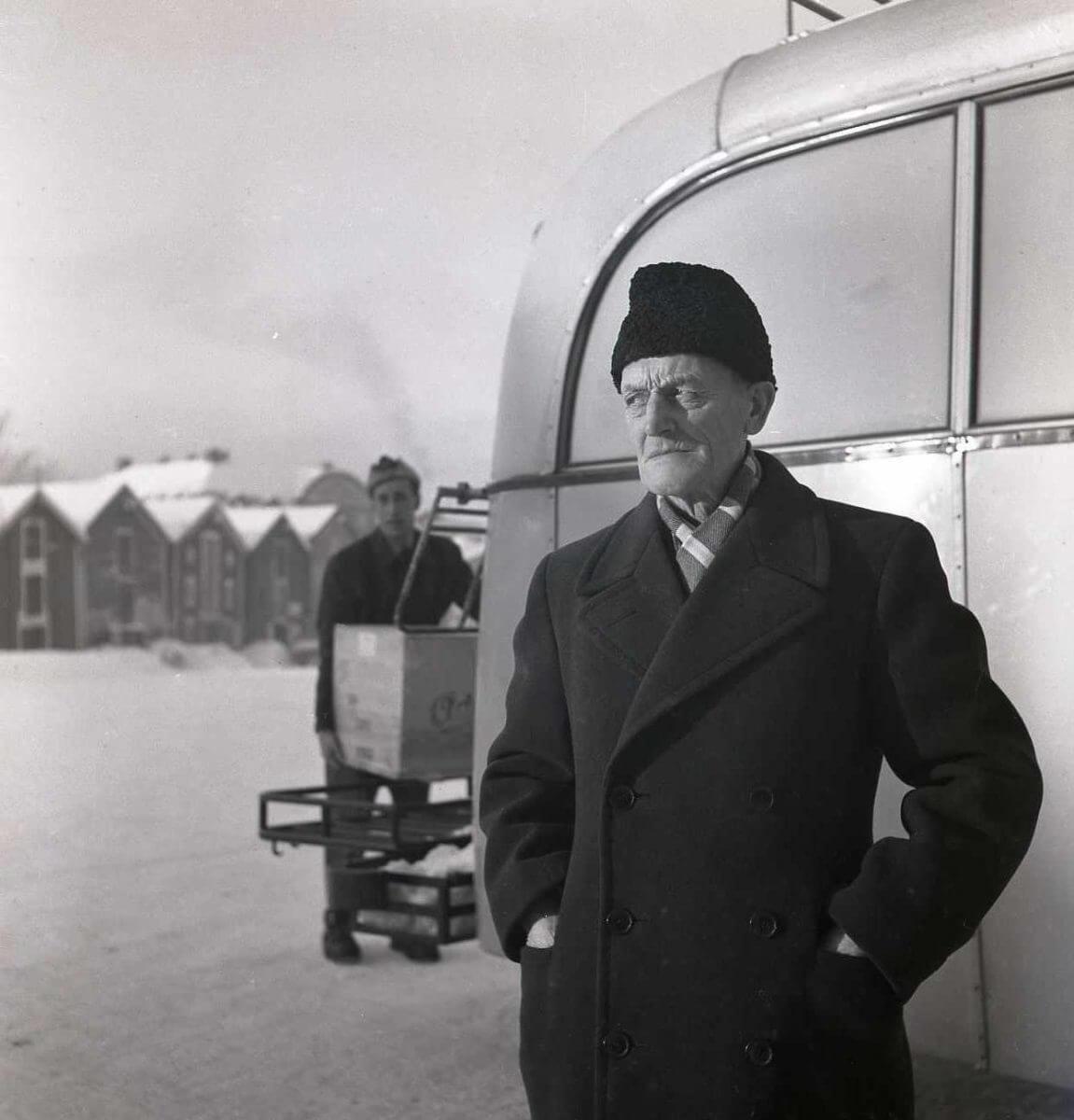 En man står framför en buss med händerna i rockfickorna.