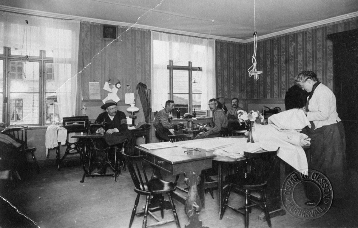 Ett arbetsrum där en man syr, en kvinna arbetar med tyg och en grupp äter vid ett bord.