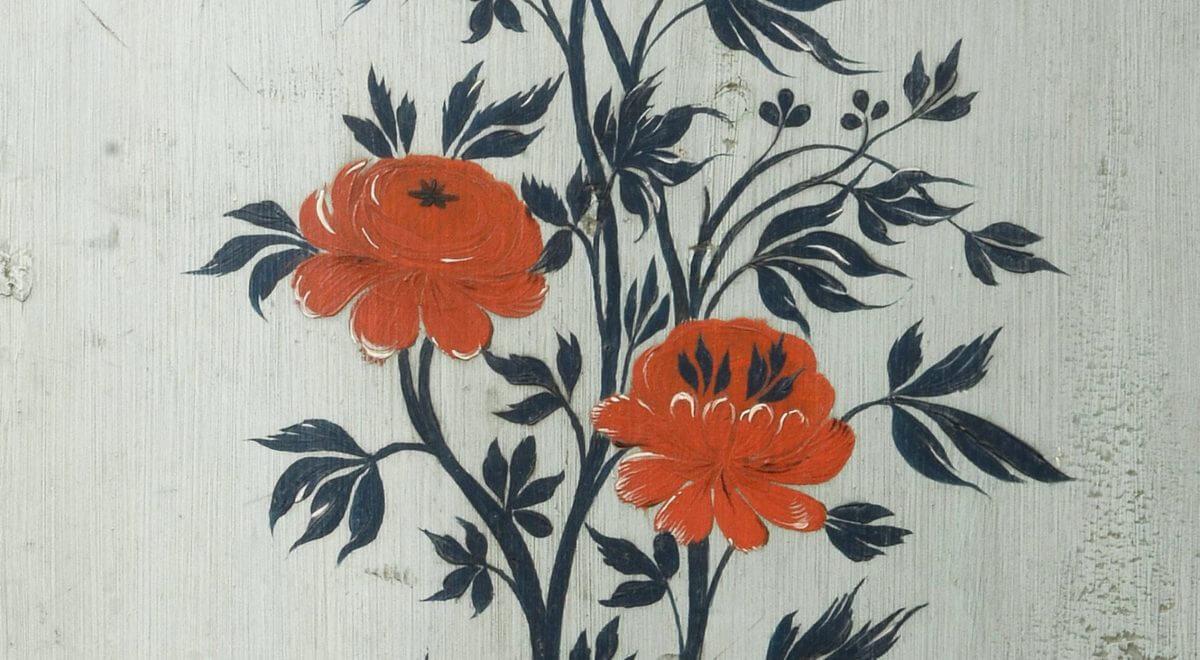 Målad vägg med blommor och blad.