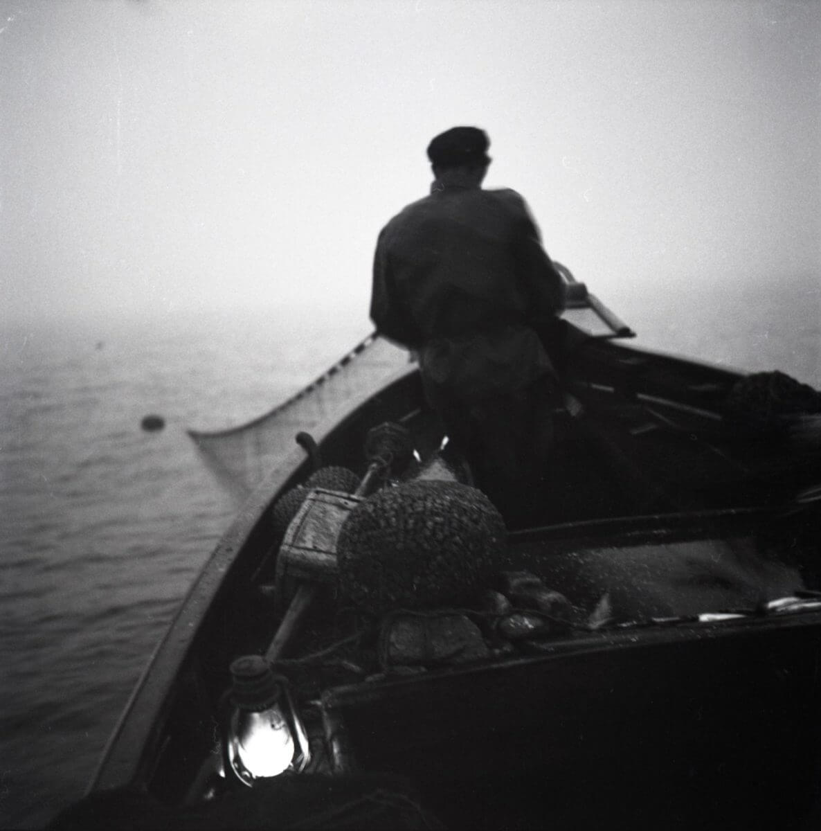 En fiskare sitter i fören på en eka och lägger i nät.