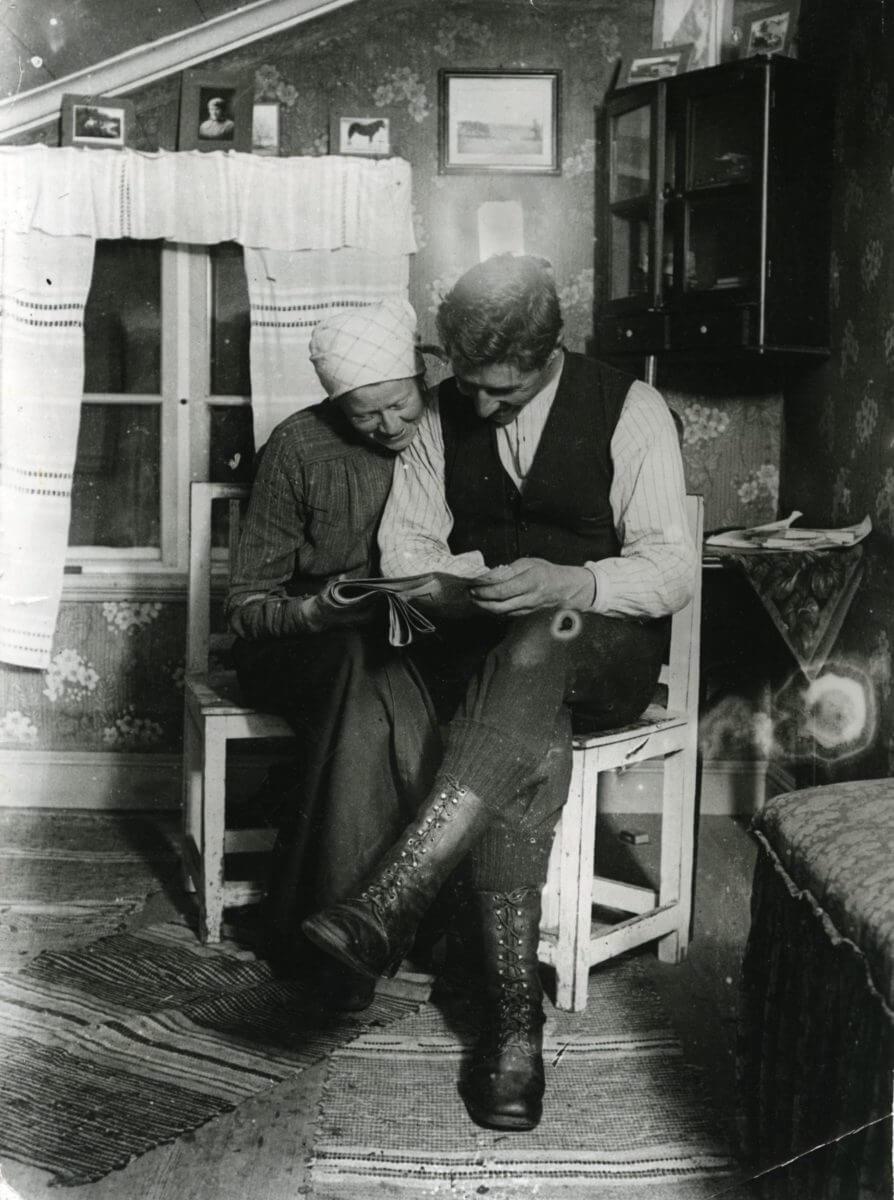 En man och en kvinna läser tidningen tillsammans i en stuga.