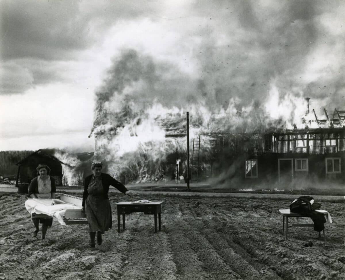 Två kvinnor bär en säng ifrån ett brinnande hus i bakgrunden.