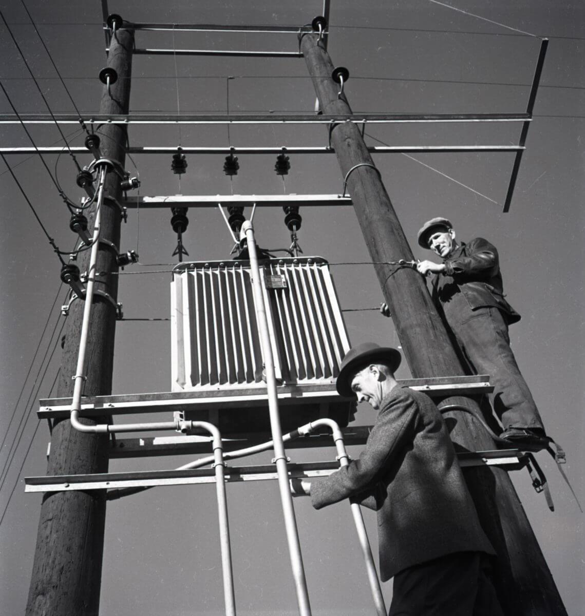 Två montörer arbetar på en elstolpe.
