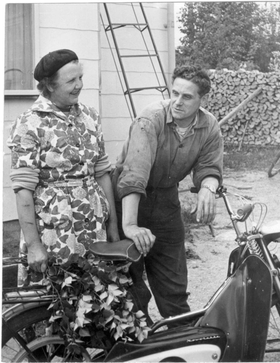 En man och en kvinna står bakom en moped.