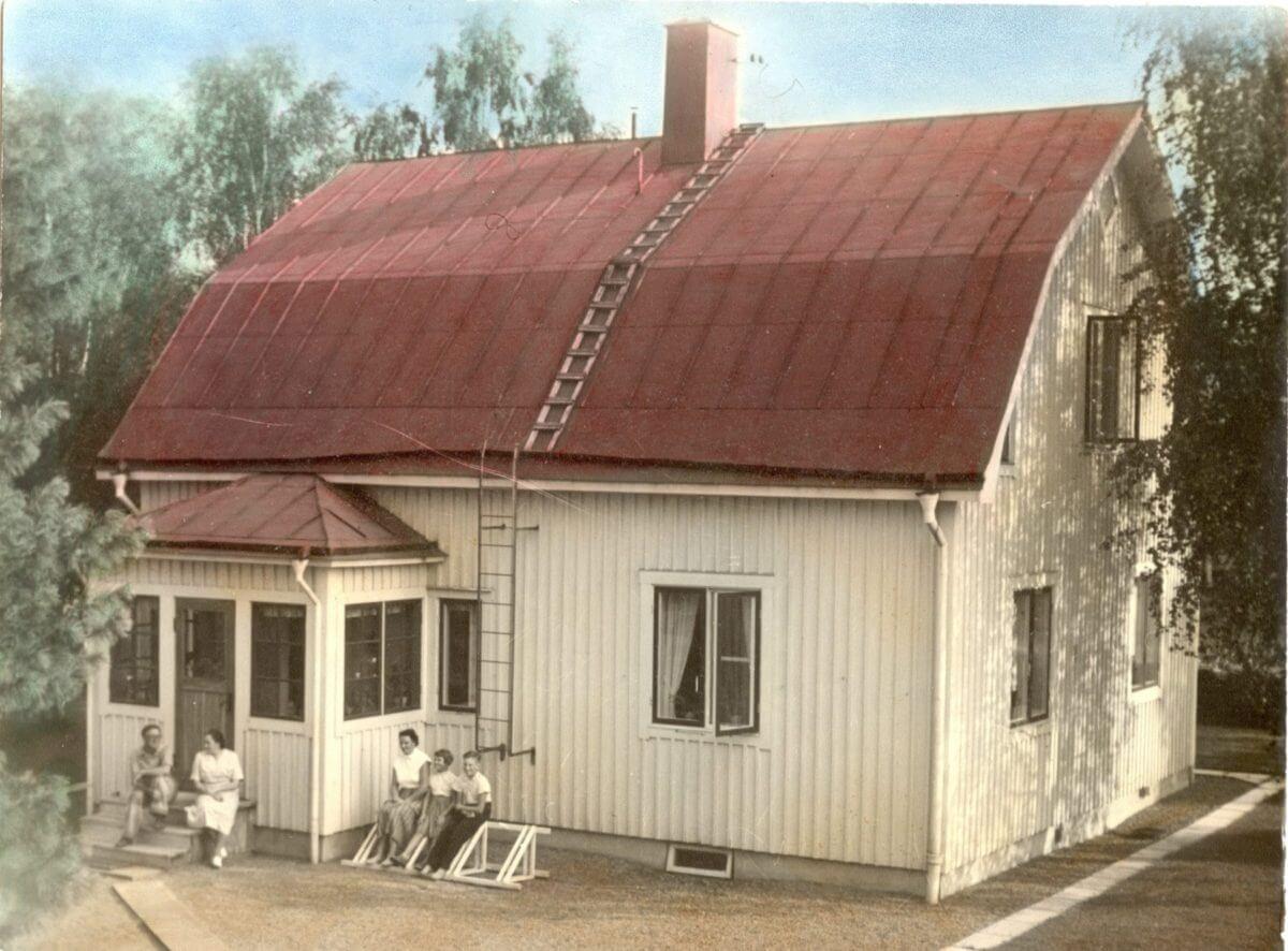 Ett hus med plåttak och träfasad. Framför huset sitter fem personer.