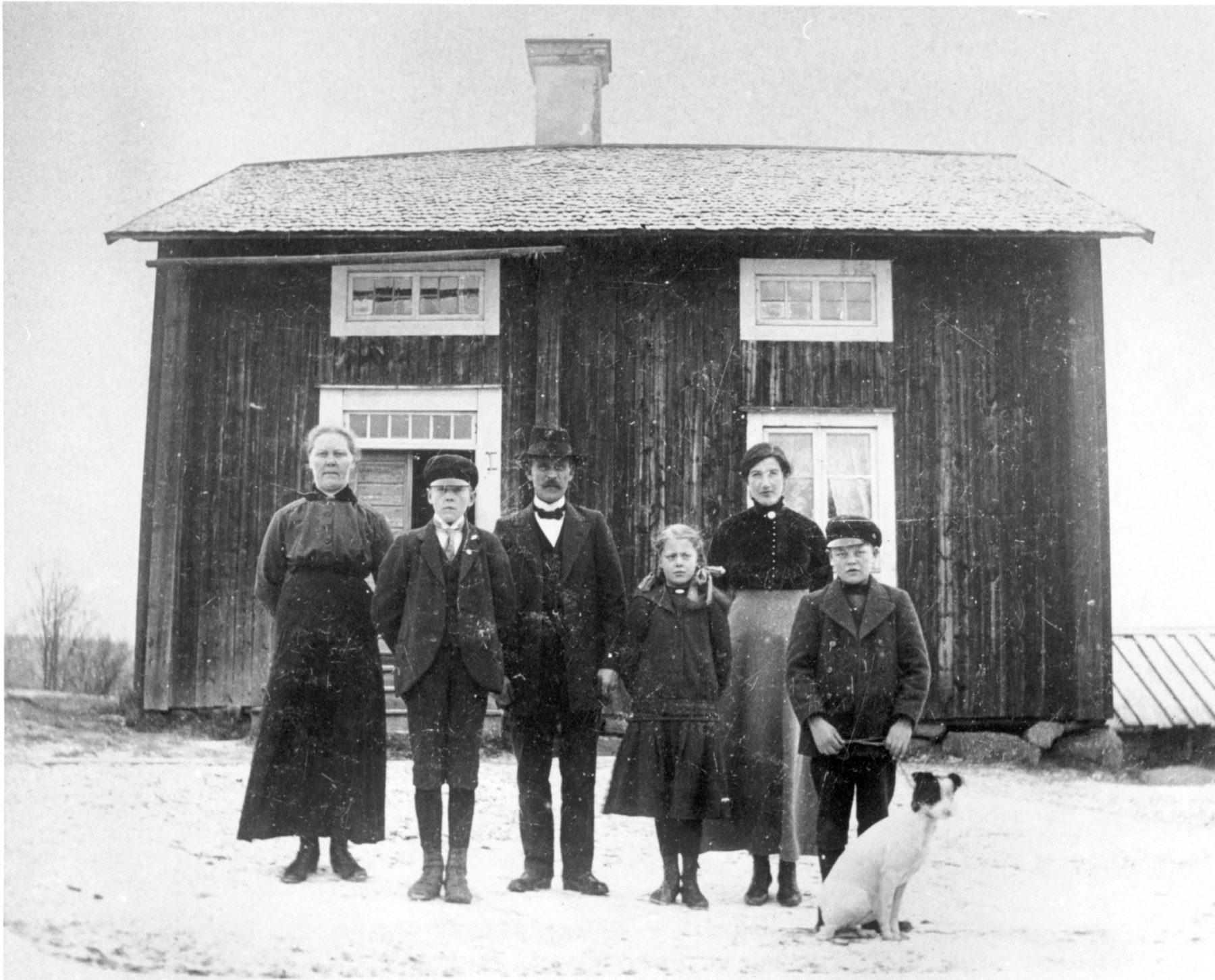 Familjebild framför hus