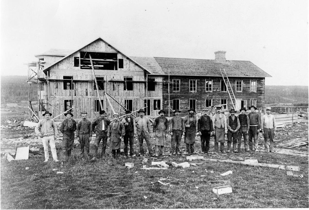 En grupp byggare poserar framför ett husbygge.