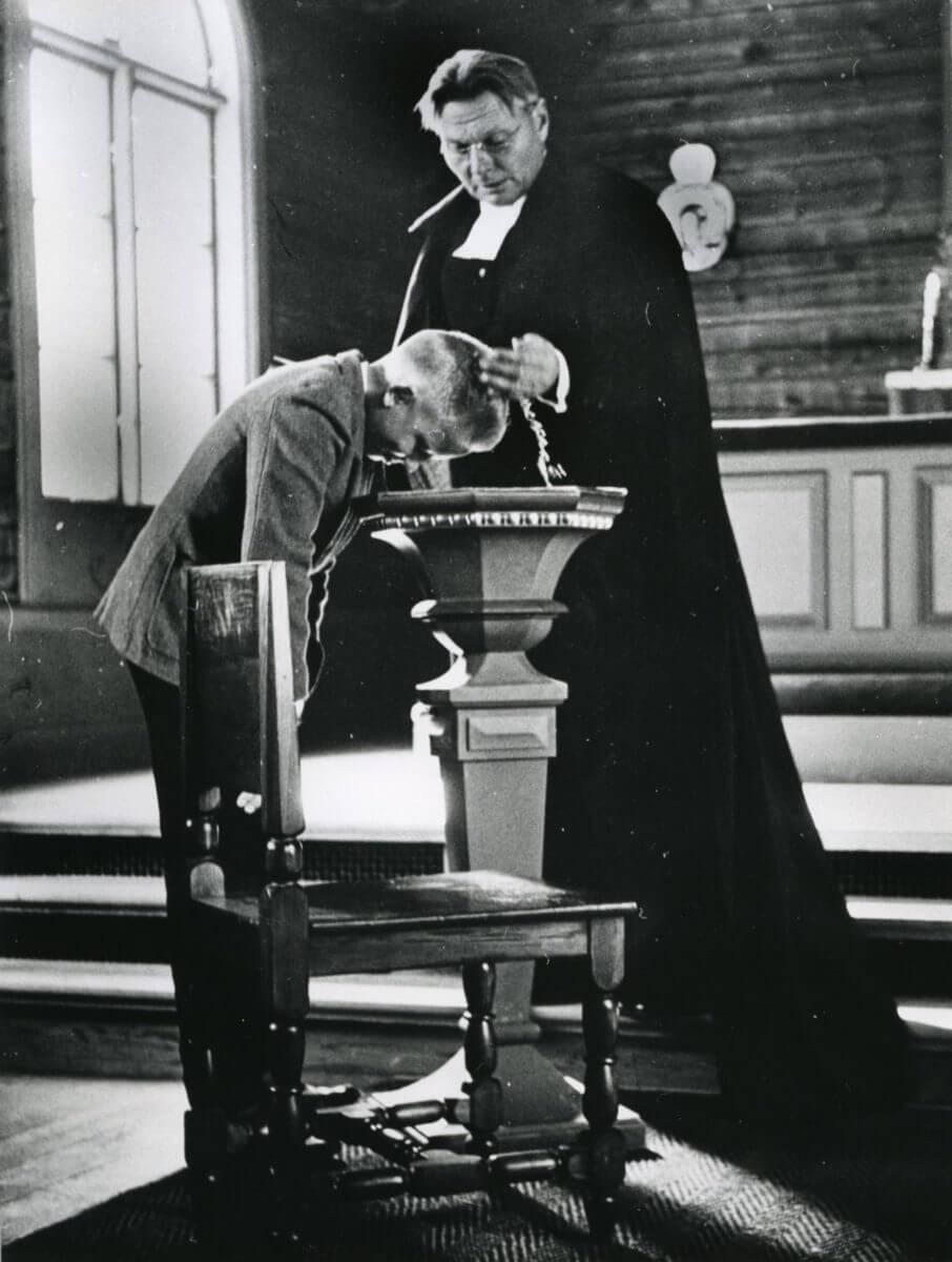 En präst döper en pojke.