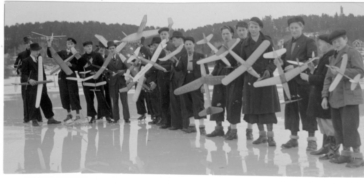 En grupp pojkar håller i varsitt modellflygplan. De står på en frusen sjö.