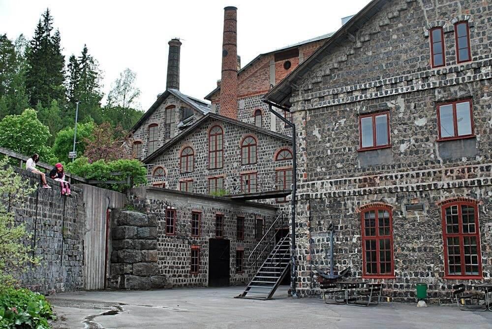 Slaggstenshus med röda fönsterfoder. Till vänster sitter tre personer på en mur.