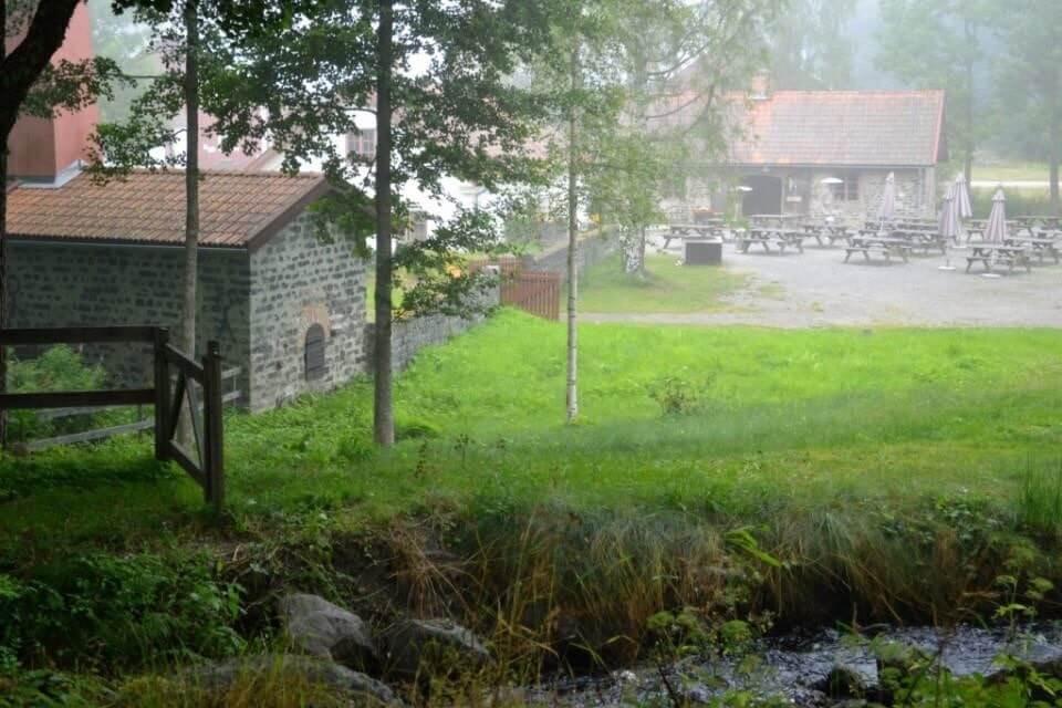 En bäck flyter framför en gård med slaggstenshus och uteservering.