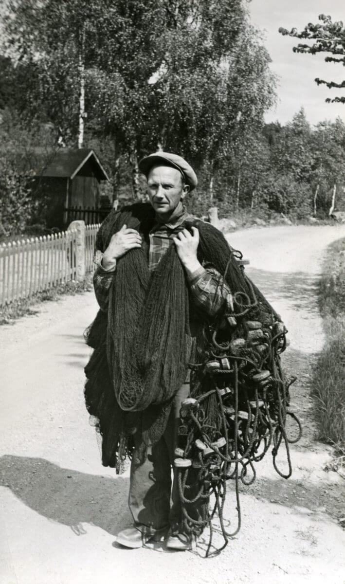 En fiskare bär nät med flöten och rep.