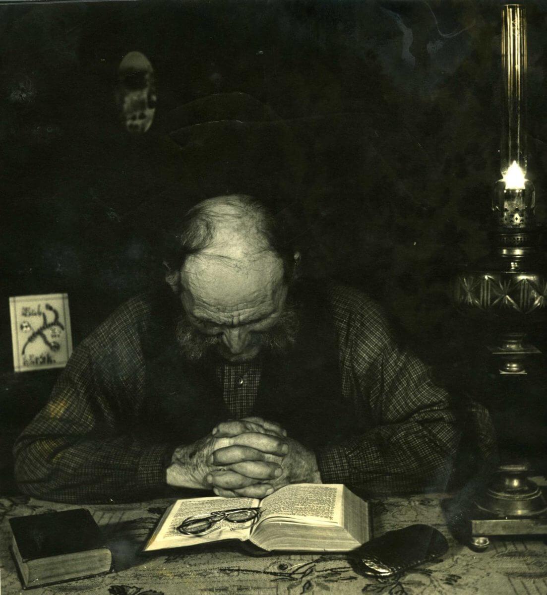 En man ber med händerna knäppta bakom en uppslagen bibel.
