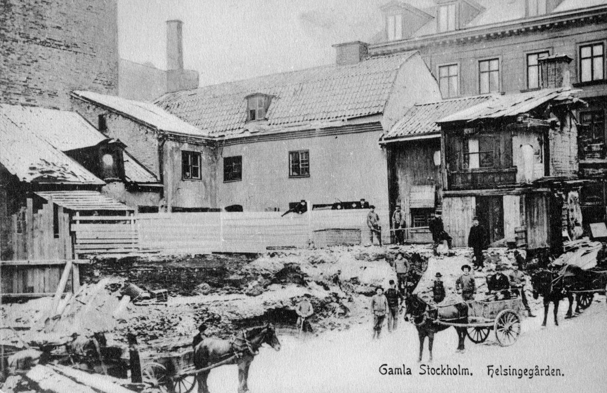 En hälsingegård i Stockholm bland andra hus. Framför husen drar hästar vagnar.