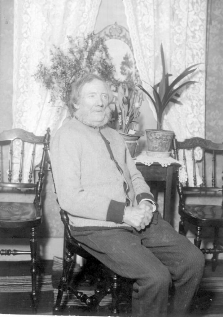 Porträtt av en man som sitter framför ett fönster med gardiner.