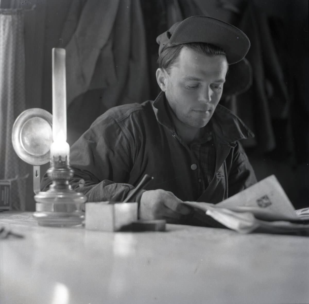 Man sitter och läser tidningen vid lampa