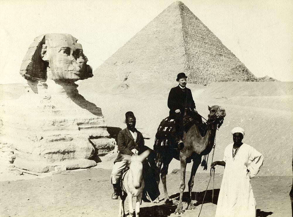 Tre män framför pyramid och sfinx.