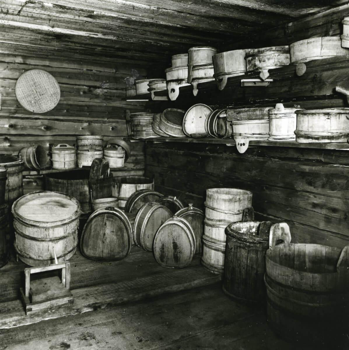 Interiör i timmerbyggnad med väggarna fyllda av träföremål.