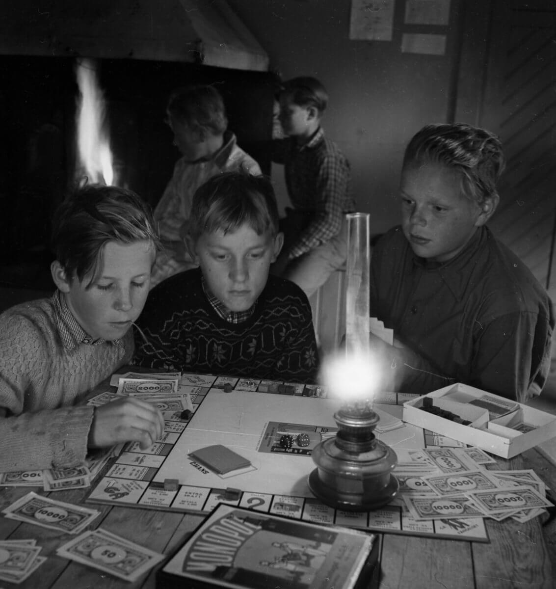 Tre pojkar sitter vid ett bord och spelar Monopol i skenet av en fotogenlampa. I bakgrunden syns en öppen spis vid vilken två pojkar står, Norrvåga 1953.