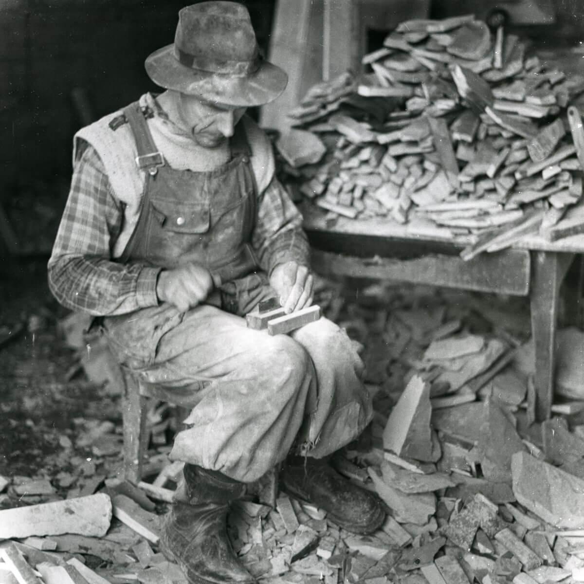 En man sitter och tillverkar Tillverkning av så kallade Los-bryn