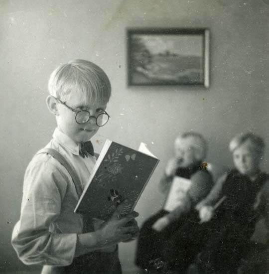 En pojke läser ur en skolbok och två barn ser på honom i bakgrunden.