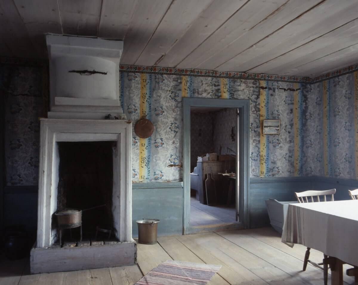 En interiör med eldstad, väggmåleri och möbler vid gården Bommars i Letsbo.