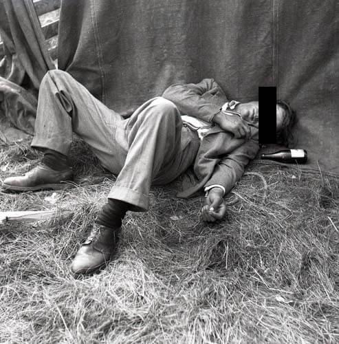 En berusad man sover ruset av sig i gräset.