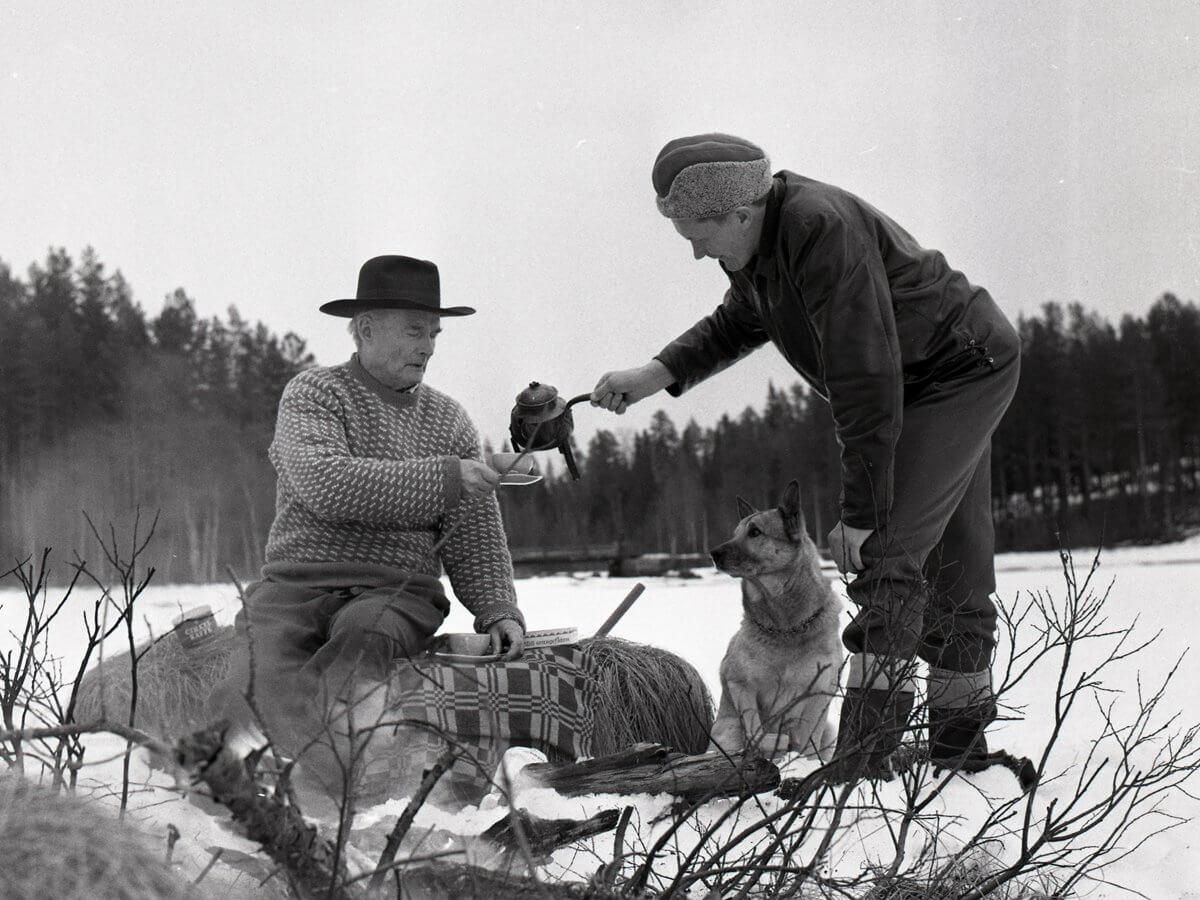 Hilding Mickelsson bjuder Albert Viksten på kaffe på Sillratjärns is och Alberts hund Nicko sitter bredvid, 4 april 1964.