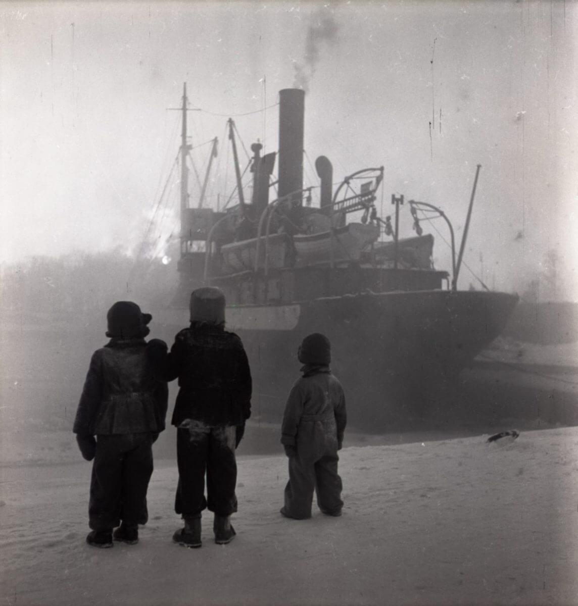 Tre barn tittar på ett fartyg som ligger inne i hamnen.
