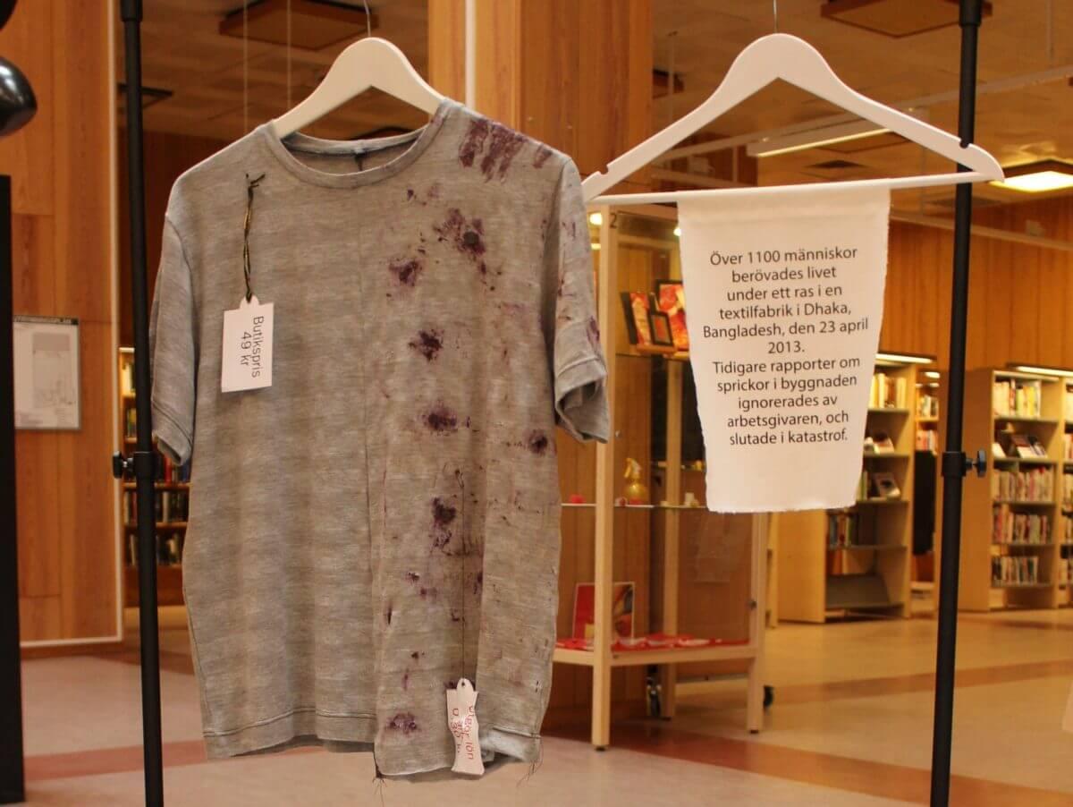 En tröja hängandes på en galge. Bredvid tröjan hänger en lapp på en galge som beskriver arbetsförhållanden i U-länder.