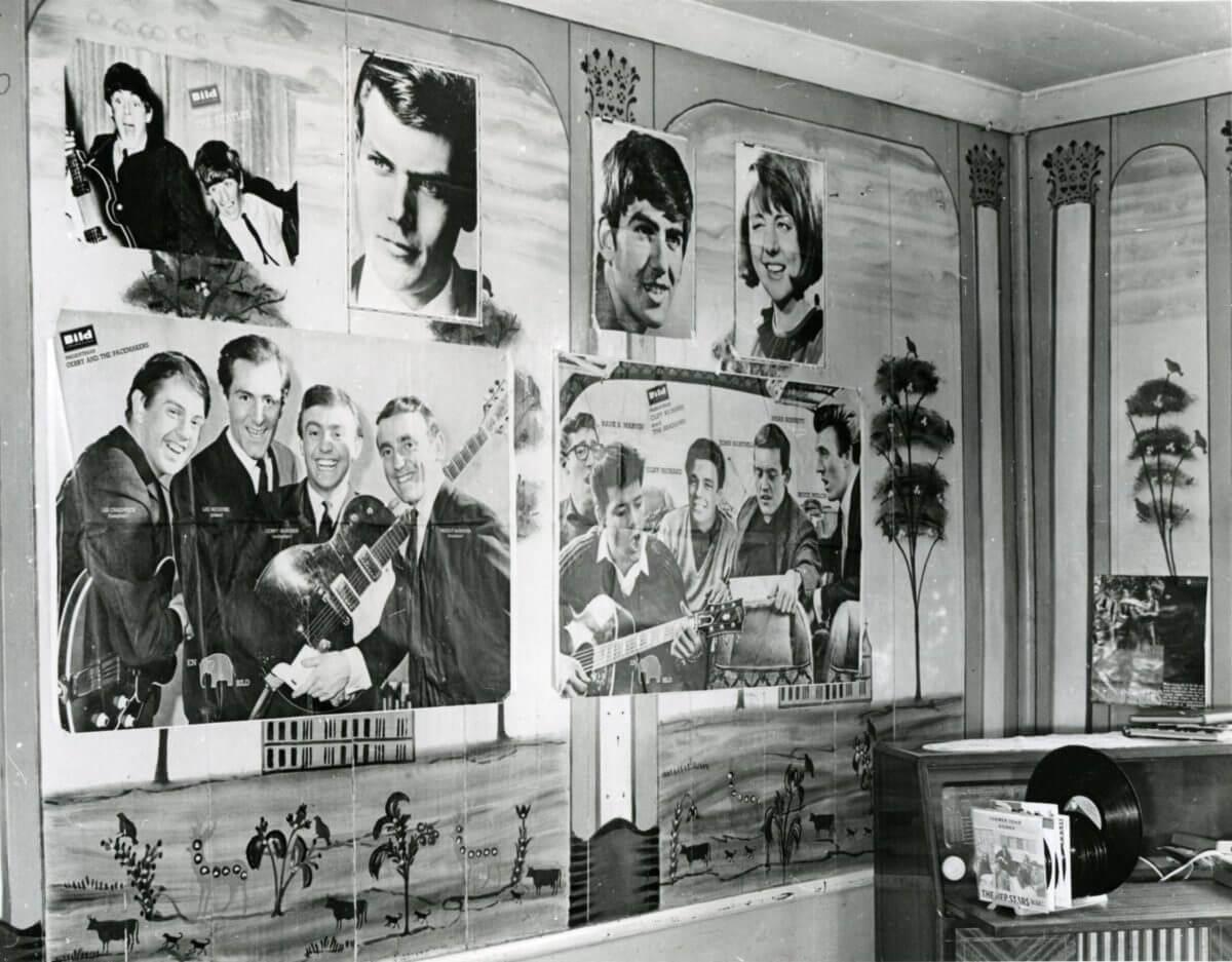 Planscher föreställande musikartister ovanpå väggmålningar.