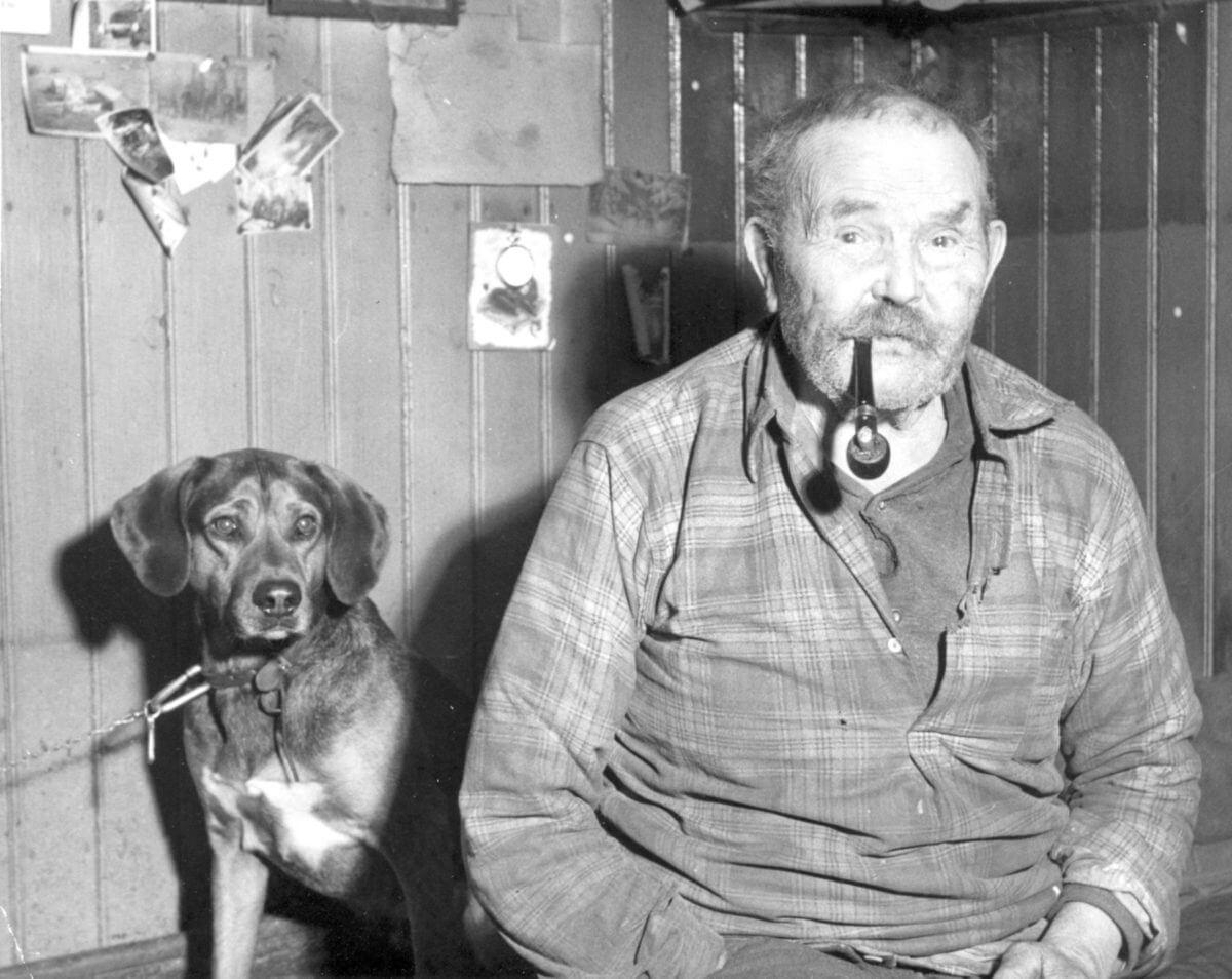 Porträtt av en man som röker pipa och en hund sitter bakom honom.