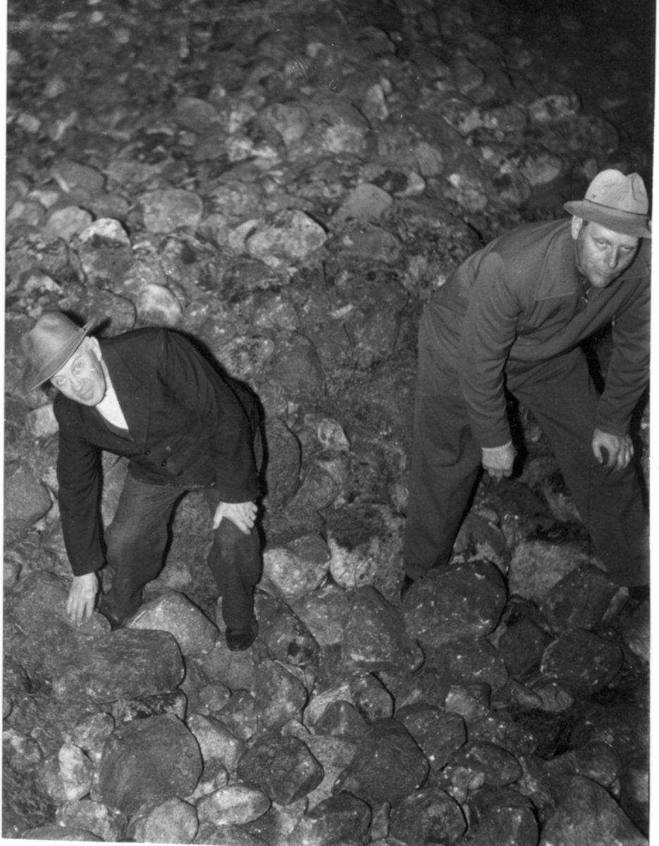 Två män står i ett stenröse.