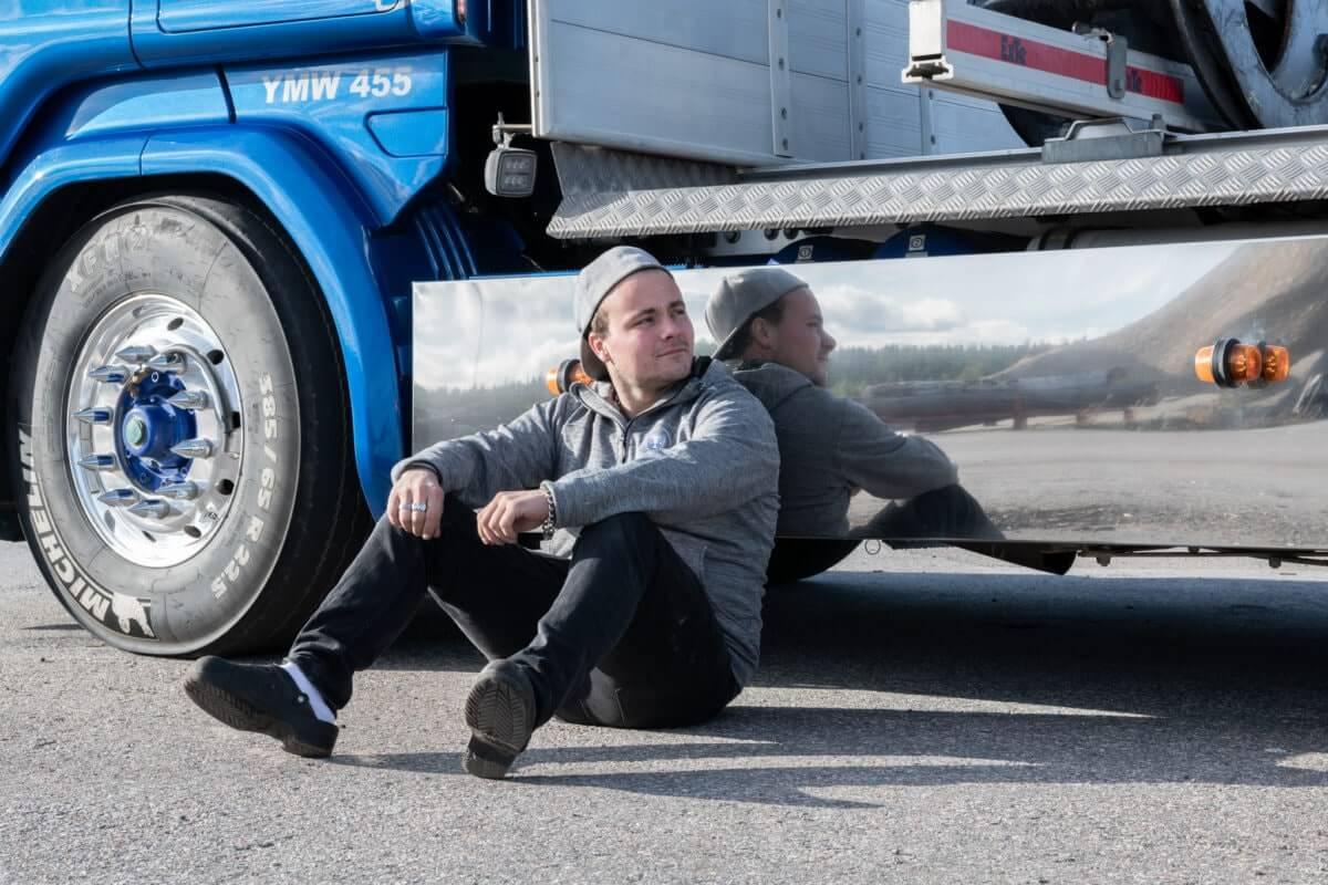 Man sitter lutad mot lastbil.