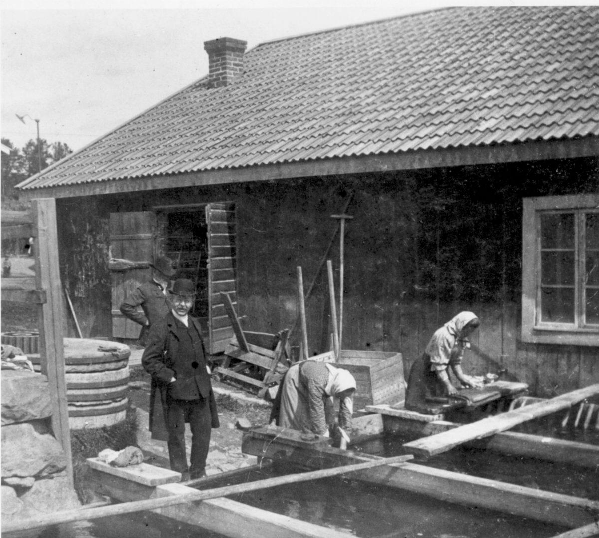 Två kvinnor arbetar intill en fiskebod i skärgården. Två män i kostym och hatt ser på.