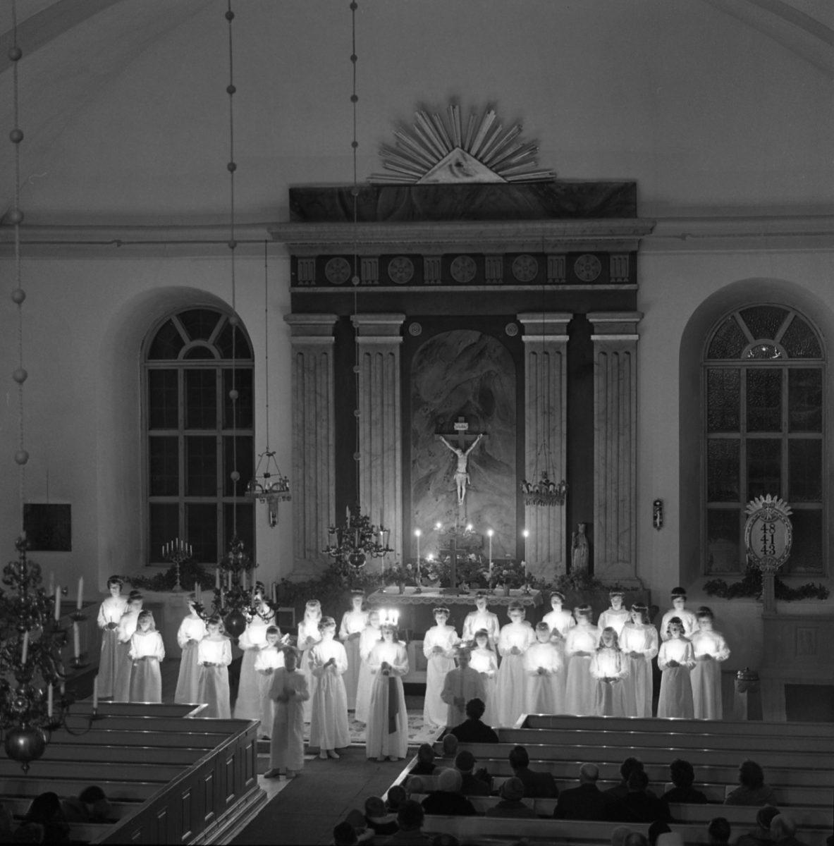 Ett luciatåg med tända ljus står uppställda längst fram i en kyrka.