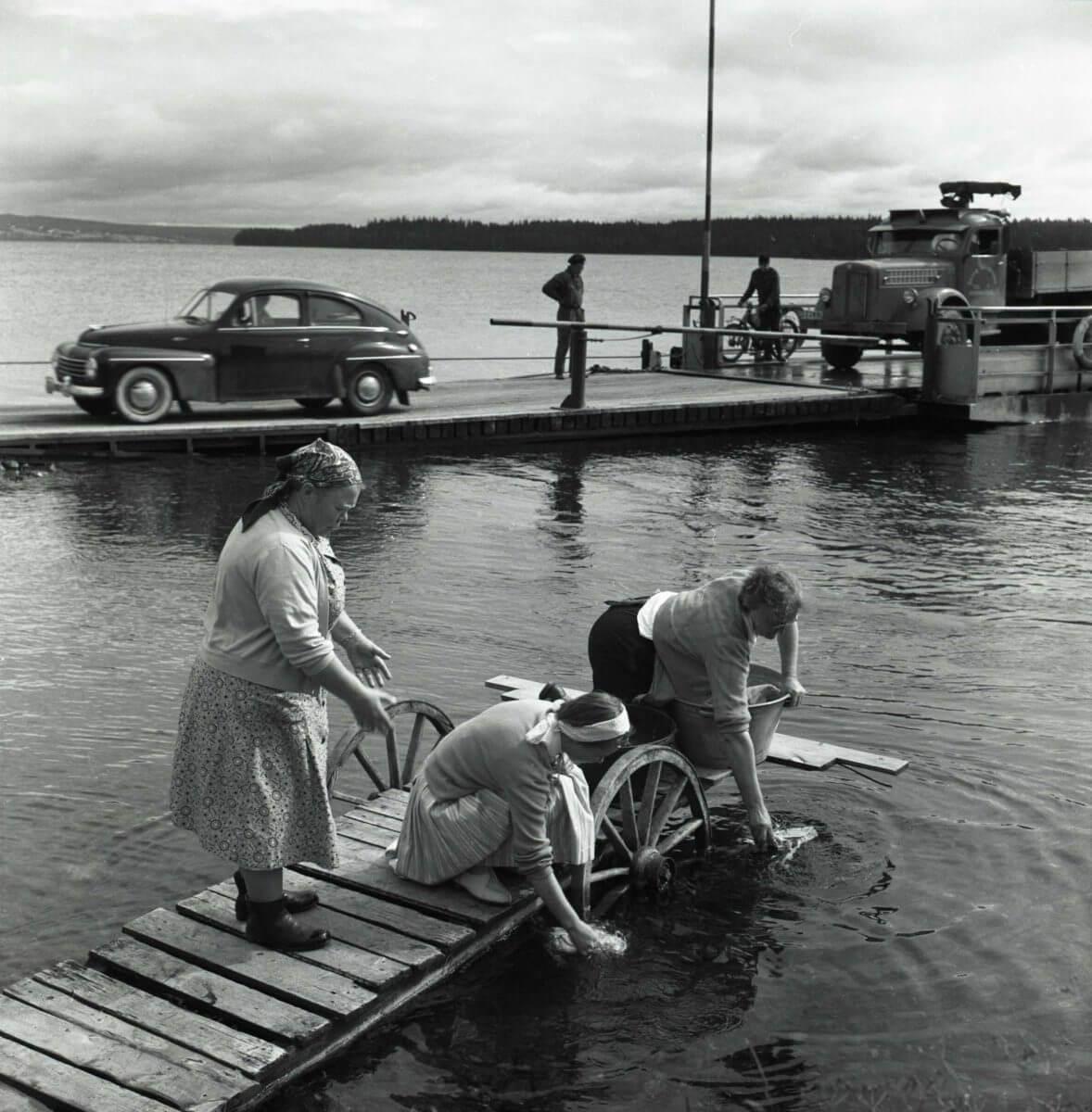 Tre kvinnor tvättar kläder från en brygga. I bakgrunden har en bilfärja dockat och fordonen kör av.