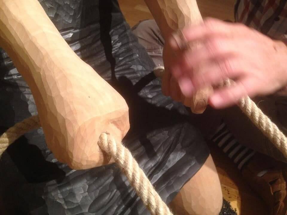 Två händer tillhörande en träskulptur håller i ett rep. En mänsklig hand håller i skulpturens ena hand.