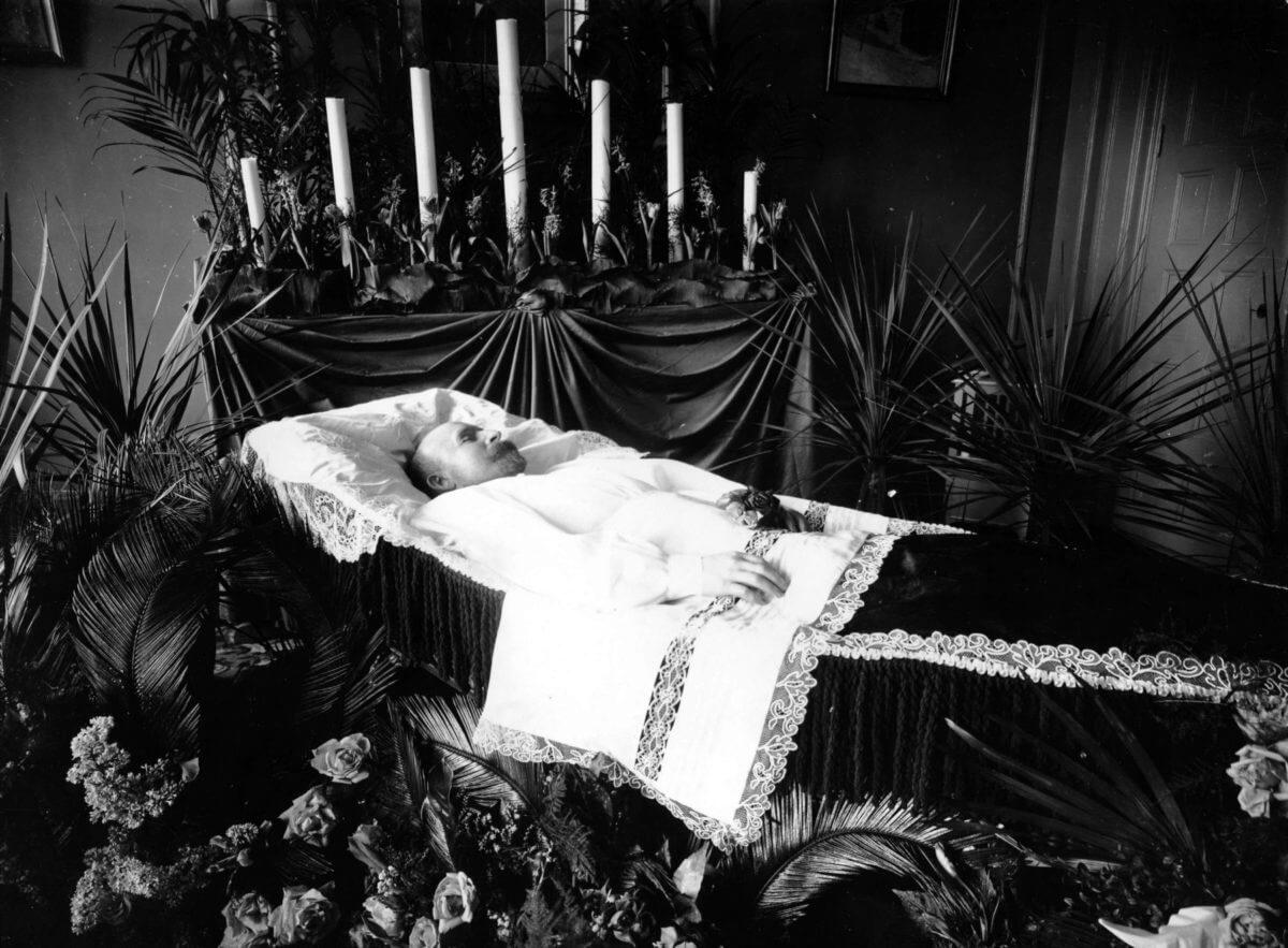 En man ligger i begravningskista under en likvaka.