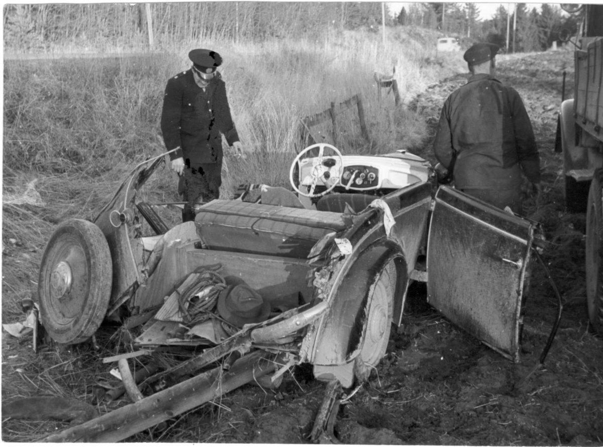 En kraschad bil ligger i ett dike och två poliser kontrollerar området.