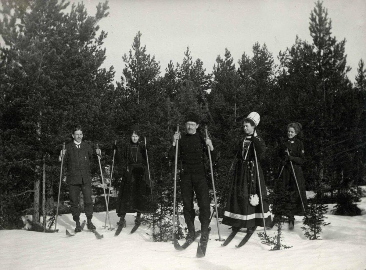 En skidgrupp står vid ett skogsbryn.
